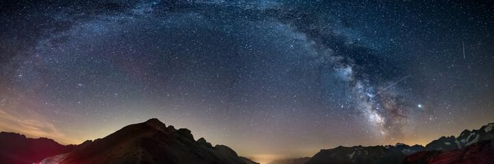 Droga Mleczna wygina się gwiaździste niebo w Alpach, Massif des Ecrins, ośrodek narciarski Briancon Serre Chevalier, Francja. Panoramiczny widok na wysokie góry i lodowce, fotografia astro, obserwacja gwiazd