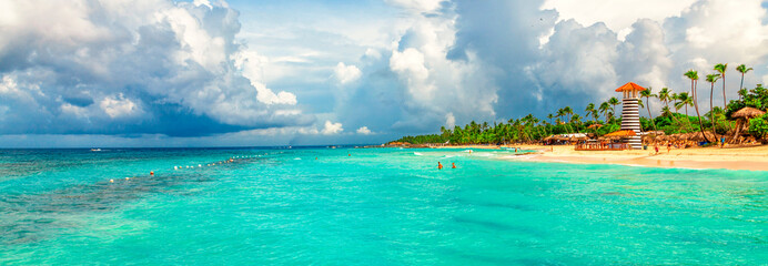 Panoramic view of the tropical beach with lighthouse in Dominican Republic. Coconut Palm trees on white sandy beach.