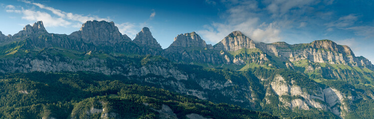 panorama mountain landscape in Switzerland with many mountain peaks in warm evening light