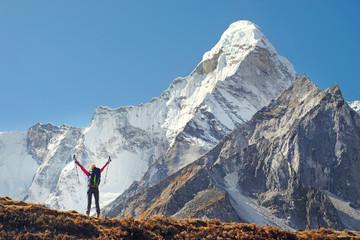 Szczęśliwy kobieta podróżnik wycieczkuje w himalajach z Ama Dablam góry tłem z plecakiem.