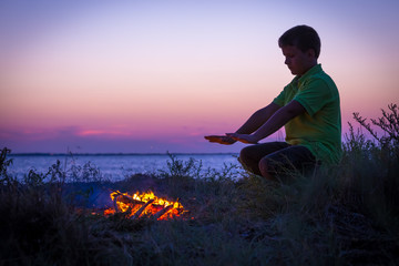 Boy warms by the campfire on the beach at sunset