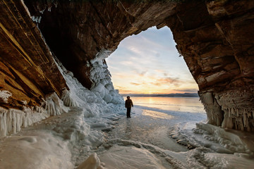 Travelling in winter, a man standing on Frozen lake Baikal with Ice cave in Siberia, Russia