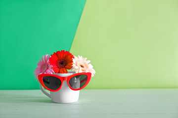 Stylish sunglasses with flowers and cup on color background