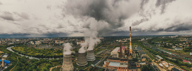 Aerial panorama of industrial area with chimneys of thermal power plant or station with smoke, railroad and other industry buildings, drone photo