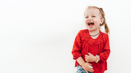 Cheerful laughing little girl in red blouse . Studio Shooting on the white background.