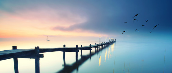 romantischer See mit Holzsteg im Herbst