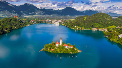 Bled, Słowenia - Panoramiczny widok na panoramę jeziora Bled (Blejsko Jezero) z kościołem pielgrzymkowym Wniebowzięcia Marii, Alp Julijskich i zamkiem Bled w tle w słoneczny letni dzień