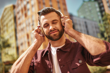 Enjoying my favorite song. Handsome young bearded man in headphones listening to the music and keeping eyes closed while standing on the street