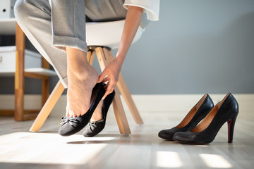 Businesswoman Changing Shoes In Office