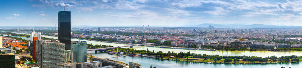 Stunning aerial panoramic cityscape view austrian capital city of Vienna.  Modern glass-concrete skyscrapers in the ancient city on the banks the Danube -of the largest river in Europe. Hot summer day