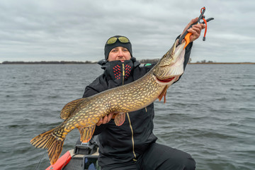 Pike fishing. Happy fisherman with big fish trophy at the boat with tackles