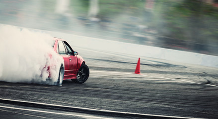 Blurred of diffusion race drift car with lots of smoke from burning tires on speed track .