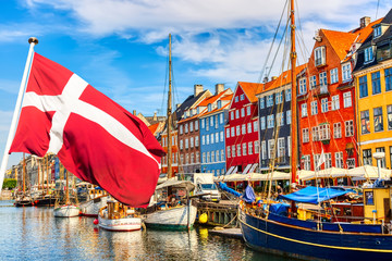 Copenhagen iconic view. Famous old Nyhavn port in the center of Copenhagen, Denmark during summer sunny day with Denmark flag on the foreground.