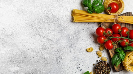 Uncooked pasta on grey stone background. Top view. Raw pasta with ingredients for cooking. Food concept. Italian food