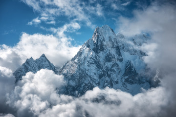 Manaslu mountain with snowy peak in clouds in sunny bright day in Nepal. Landscape with high snow covered rocks and blue cloudy sky. Beautiful nature. Fairy scenery. Aerial view of Himalayan mountains