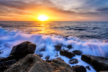 The stunning seascape with the colorful sky and water foam at the rocky coastline of the Black Sea
