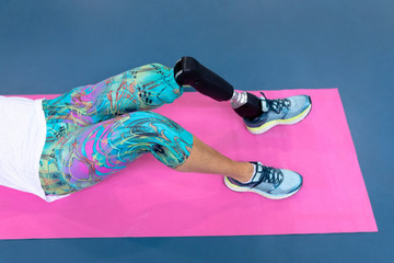 Disabled active senior woman exercising on exercising mat in sports center