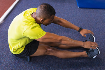 Male athletic exercising in fitness center