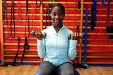 Woman looking at camera while exercising with dumbbell in sports center