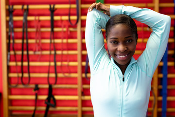 Woman stretching arms in sports center