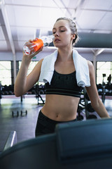 Fit woman having water while exercising on a treadmill