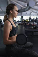Woman exercising with dumbbell in fitness center
