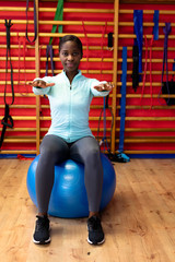 Woman exercising with exercise ball in sports center