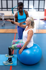 Trainer assisting disabled senior woman in sports center