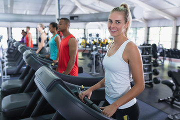 Fit woman exercising on treadmill in fitness center