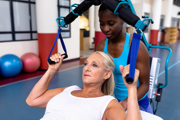 Female trainer helping disabled active senior woman to exercise in sports center