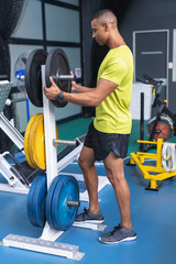 Fit man removing barbell from barbell stand in fitness center