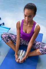 Fit woman performing yoga on a exercise mat in fitness center