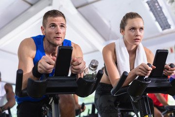 Male and female friend exercising on exercise bike in fitness center