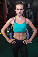 Female athletic standing with hands on hip in fitness center