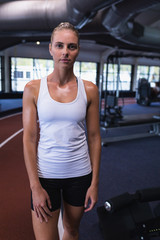 Female athletic looking at camera while standing in fitness center