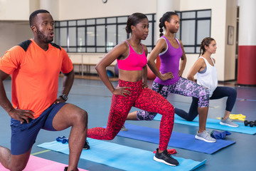 Fit people performing yoga together on a exercise mat in fitness center
