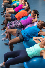 Fit people exercising on exercise ball in fitness center