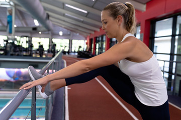 Beautiful woman exercising on railing in modern sports center