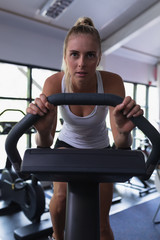Fit woman working out on exercise bike in fitness center