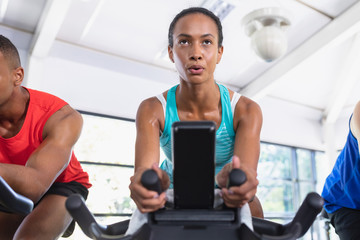 Fit woman exercising on exercise bike in fitness center