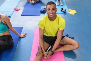 Fit man relaxing on a exercise mat in fitness center