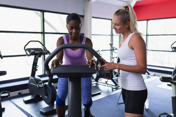 Female trainer assisting woman to work out on exercise bike