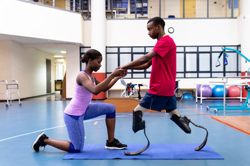 Female physiotherapist helping disabled man walk with prosthetic leg in sports center