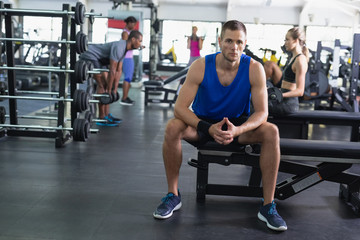 Fit man relaxing on a bench in fitness center