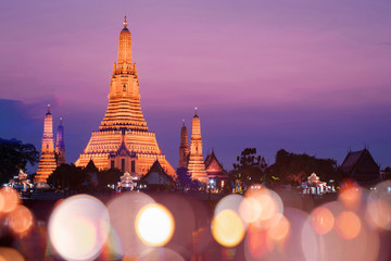 Wat Arun temple with sunset and blur bokeh at foreground during sunset.