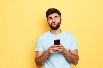 brunette handsome puzzled hesitated man using smartphone isolated over yellow background, thoughtful man doesn't want to answer the message