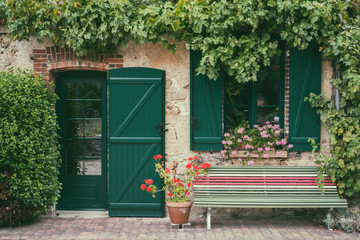 beautiful tradiitional little french house entrance and facade surronded by beautiful picturesque tradiitional little french house entrance and facade surronded by vine anf flowerswith a bench outside