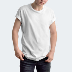 Attractive slim guy in a blank T-shirt and dark jeans on a white studio background.