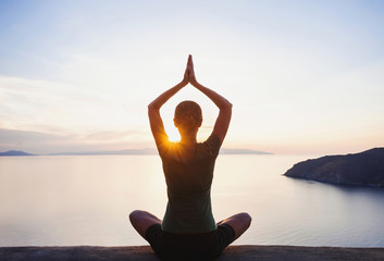 Young woman practicing yoga near the sea at sunset. Harmony, meditation  and travel concept. Healthy lifestyle