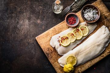 Raw cod fish fillet with lemon slices and herbal salt on rustic wooden cutting board on dark background, top view. Fish cooking preparation. Healthy diet food. Border. Copy space